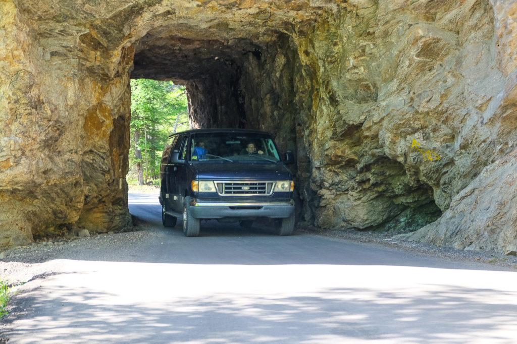 van going through tunnel on needles highway in Custer state park, South Dakota